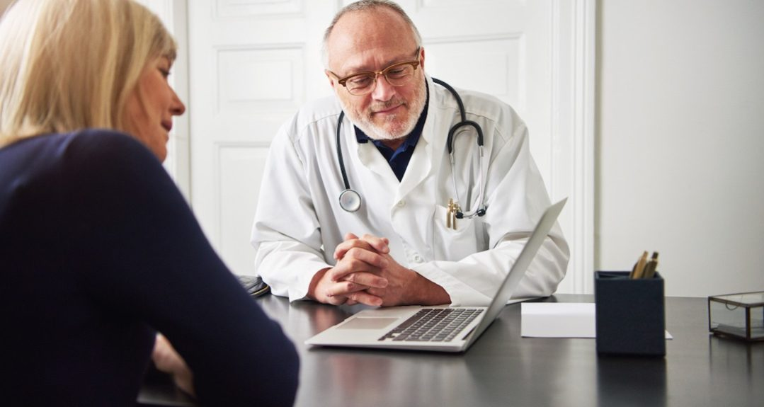Medic and patient at laptop in office